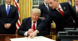 White House Chief of Staff Reince Priebus (R) directs U.S. President Donald Trump, flanked by Vice President Mike Pence (L), where to sign the document to confirming James Mattis his Secretary of Defense, his first signing in the Oval Office in Washington, U.S. January 20, 2017. REUTERS/Jonathan Ernst